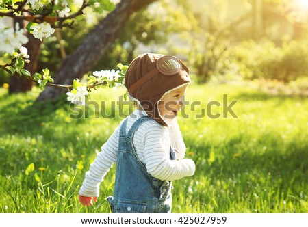 Boy playing in aviator hat in the garden - stock photo