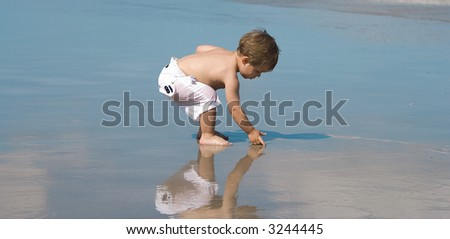 Boy playing in ocean. Reflection of sky in the background. - stock photo