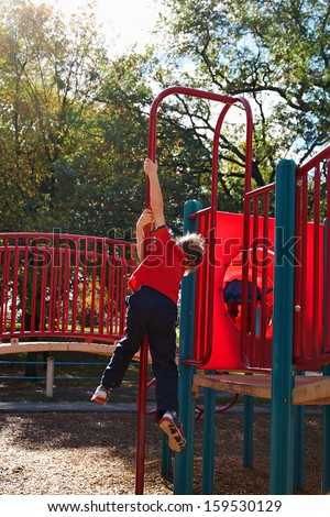 Boy playing in playground at  autumn - stock photo