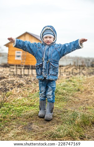 boy playing in the garden with her hands wide open - stock photo