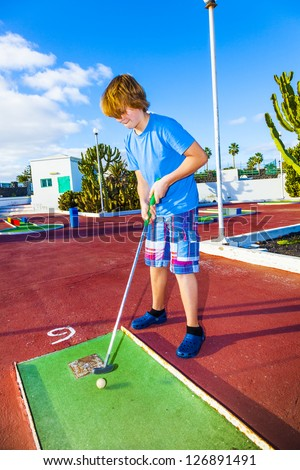 boy playing mini golf in the course