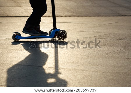 boy playing mini scooter, kick scooter in park - stock photo