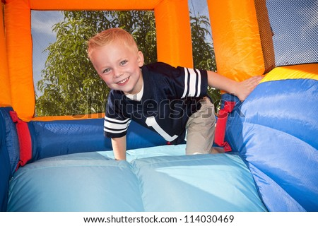Boy playing on and inflatable Side - stock photo