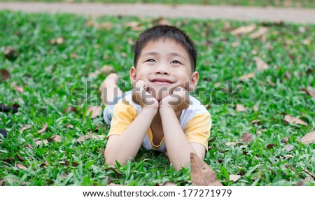 boy playing on green grass - stock photo