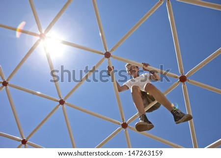 boy playing on high up on playground, view from ground toward sun - stock photo