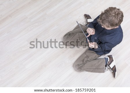 Boy playing on tablet pc - stock photo