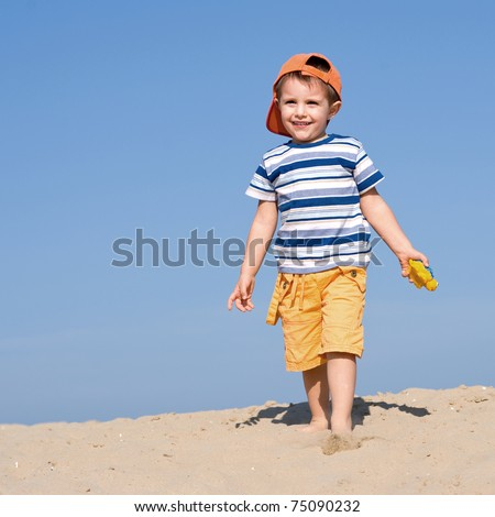 Boy playing on the beach. - stock photo