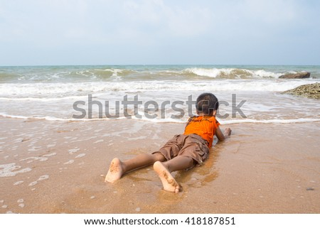 boy playing on the beach in the water