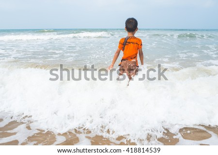 boy playing on the beach in the water - stock photo