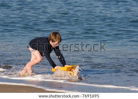 Boy playing on the beach with a yellow truck