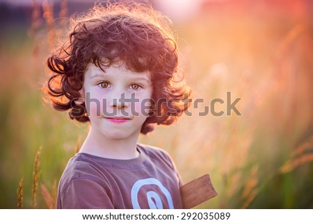 boy playing on the filed in sunset - stock photo