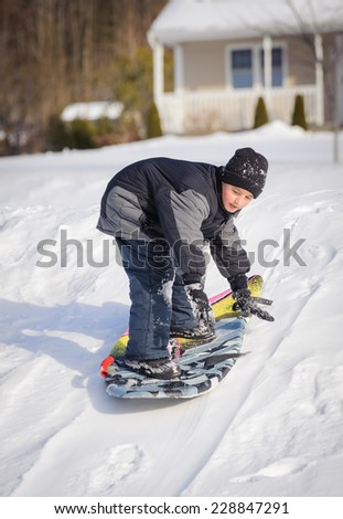 Boy playing on the snow - stock photo
