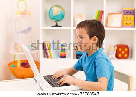 Boy playing or working on laptop computer in his room - stock photo