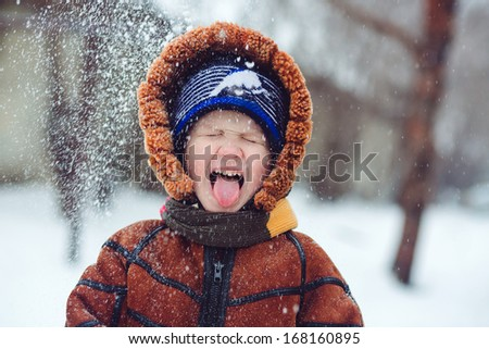 Boy playing snowballs and snow catches tongue - stock photo