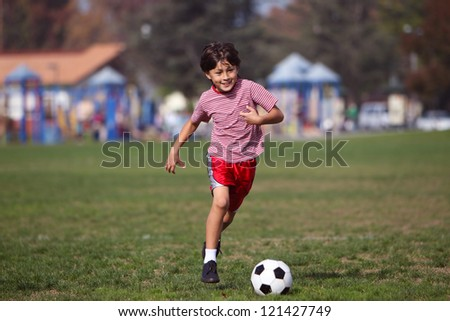 Boy playing soccer in the park - Authentic action with soccer ball - copy space right and left - landscape format - stock photo