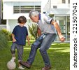 Boy playing soccer with his grandfather in garden in front of a house - stock photo