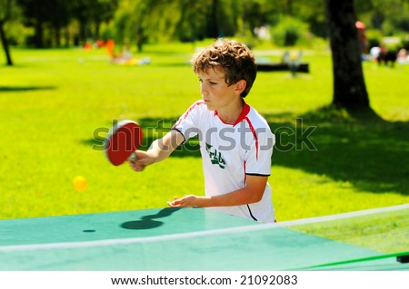 boy playing table tennis in the park - stock photo