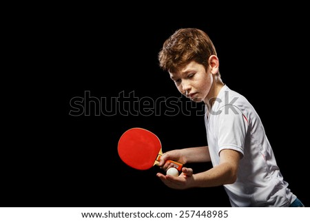 Boy playing table tennis on a black background - stock photo