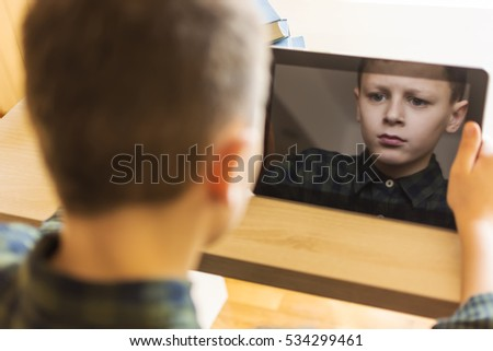 Boy Playing Tablet Game. Expressive Face in Reflection.