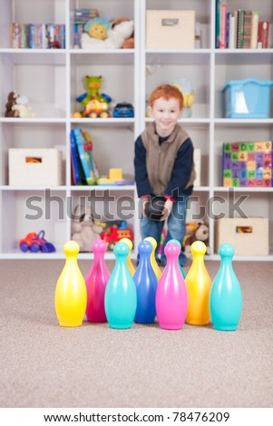 Boy playing ten pin bowling in play room - stock photo