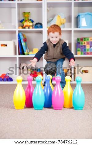 Boy playing ten pin bowling in play room - stock photo