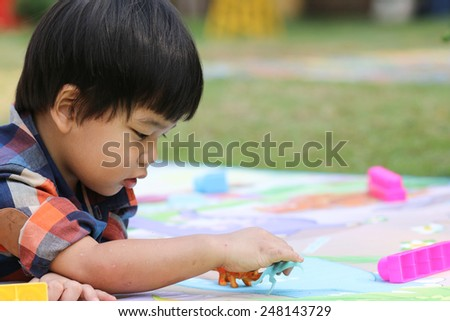 boy playing toy, children in playground.