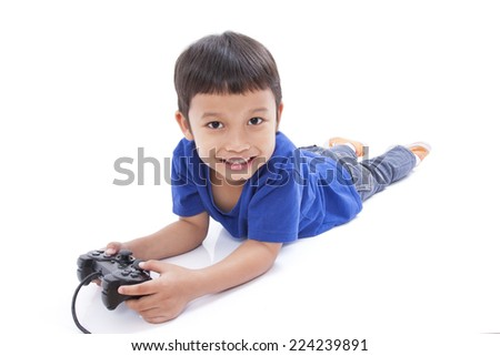 Boy playing video game and lying on the floor  - stock photo