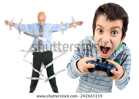 Boy playing video games and dad glued to the wall with duct tape in the background - stock photo
