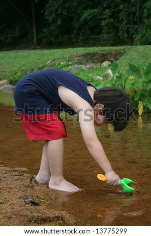 Boy playing water and sand by the river - stock photo