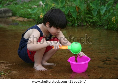 Boy playing water by the river in the afternoon - stock photo