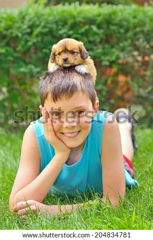 boy playing with a puppy in garden - stock photo