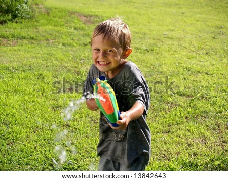 boy playing with a squirt gun squirting photographer - stock photo