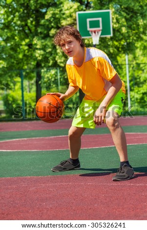 Boy playing with ball alone during basketball game - stock photo