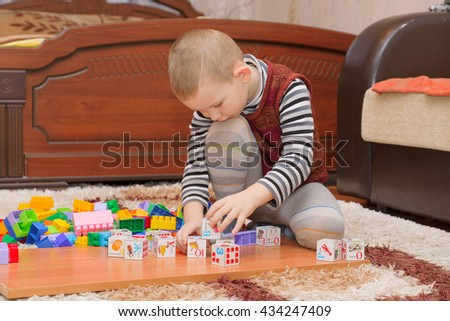 boy playing with blocks and train on the floor - stock photo