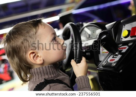 Boy playing with car simulator in the amusement park - stock photo