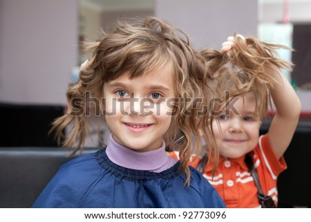 Boy playing with girls hair