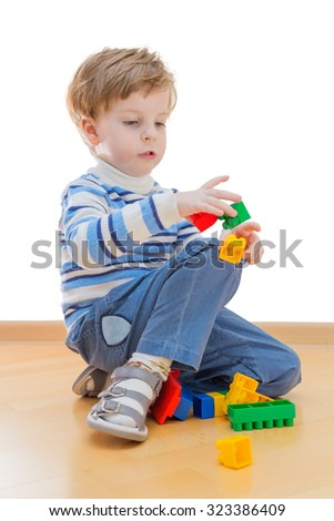 Boy playing with plastic construction isolated on white background - stock photo