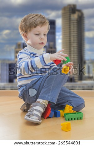 Boy playing with plastic construction with contemporary buildings in background - stock photo
