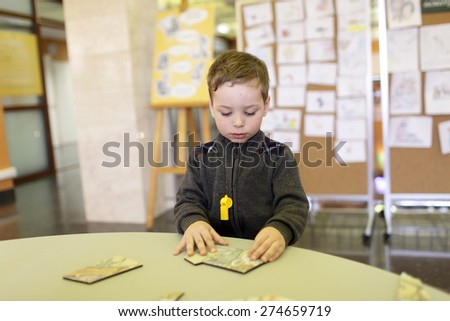 Boy playing with puzzle in the classroom - stock photo