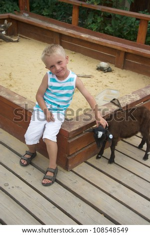 Boy playing with small black goat in sandbox - stock photo