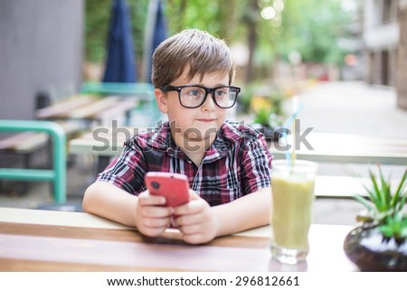 Boy playing with smartphone outdoors. Shallow depth of field  - stock photo