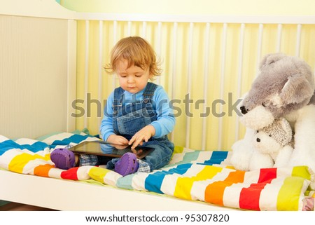 Boy playing with tablet pc sitting in the bed in nursery room