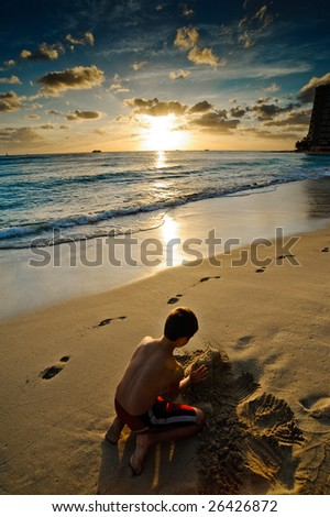 Boy playing with the sand at sunset - stock photo