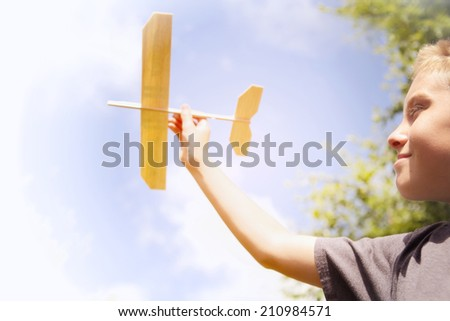 Boy playing with Toy airplane in the sky - stock photo
