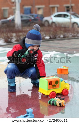 Boy playing with toy cars at outdoor playground in spring - stock photo