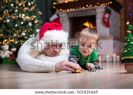 Boy playing with toy cars with his parents under the christmas tree