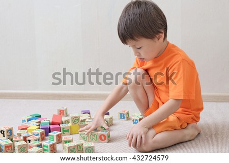 Boy playing with toy cubes in the room