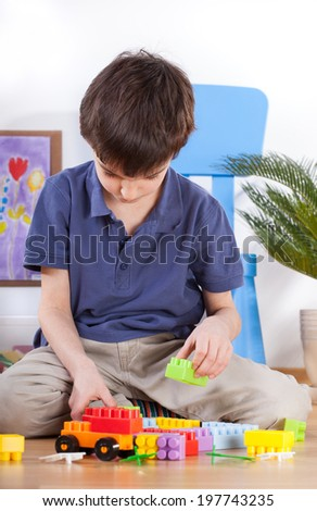 Boy playing with toys in playroom, vertical - stock photo