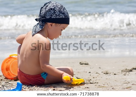 Boy playing with toys on beach - stock photo