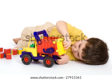 Boy playing with truck and blocks over white background